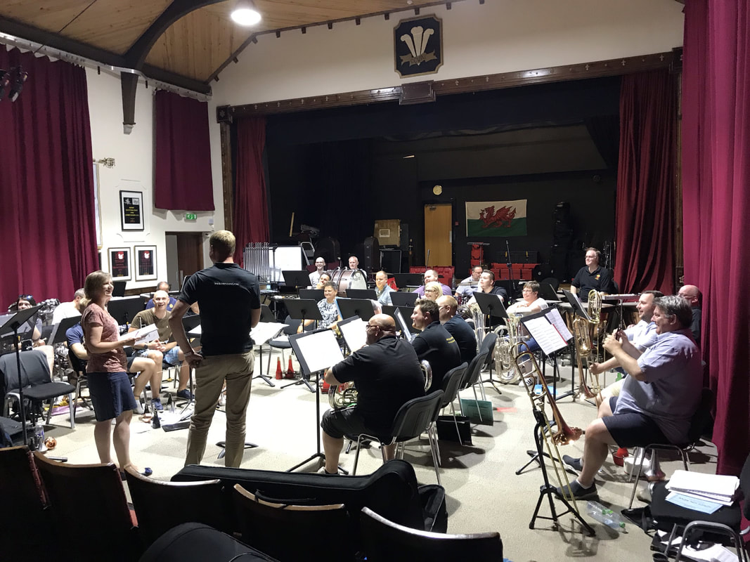 Discussing score at rehearsal of Slate, Sea and Sky, Cory Band, Tom Hutchinson (cornet), Philip Harper (conductor), Parc Hall, Treorchy, Wales, 19 July 2018