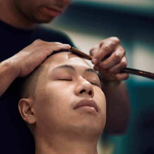 Man Relaxing in barber's chair as barber uses strait razor on forehead