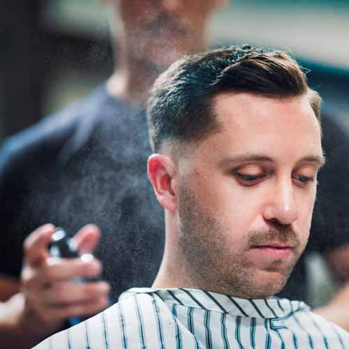 Man is sprayed with cologne after receiving haircut and shave