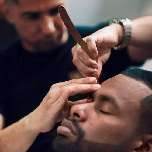 Man relaxes with eyes closed as barber shaves with a strait razor