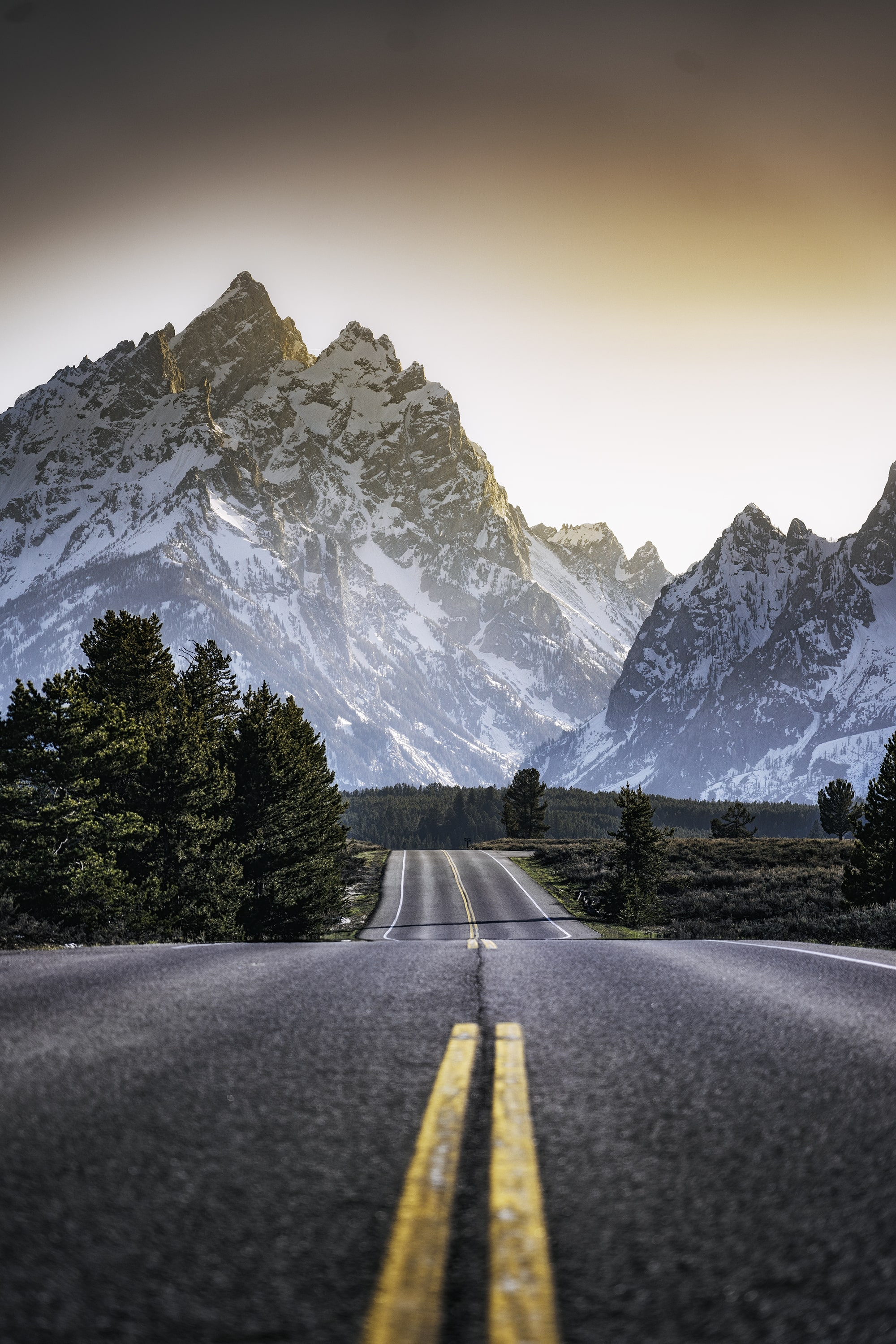 Shot from the middle of the road leading to a snowy mountain