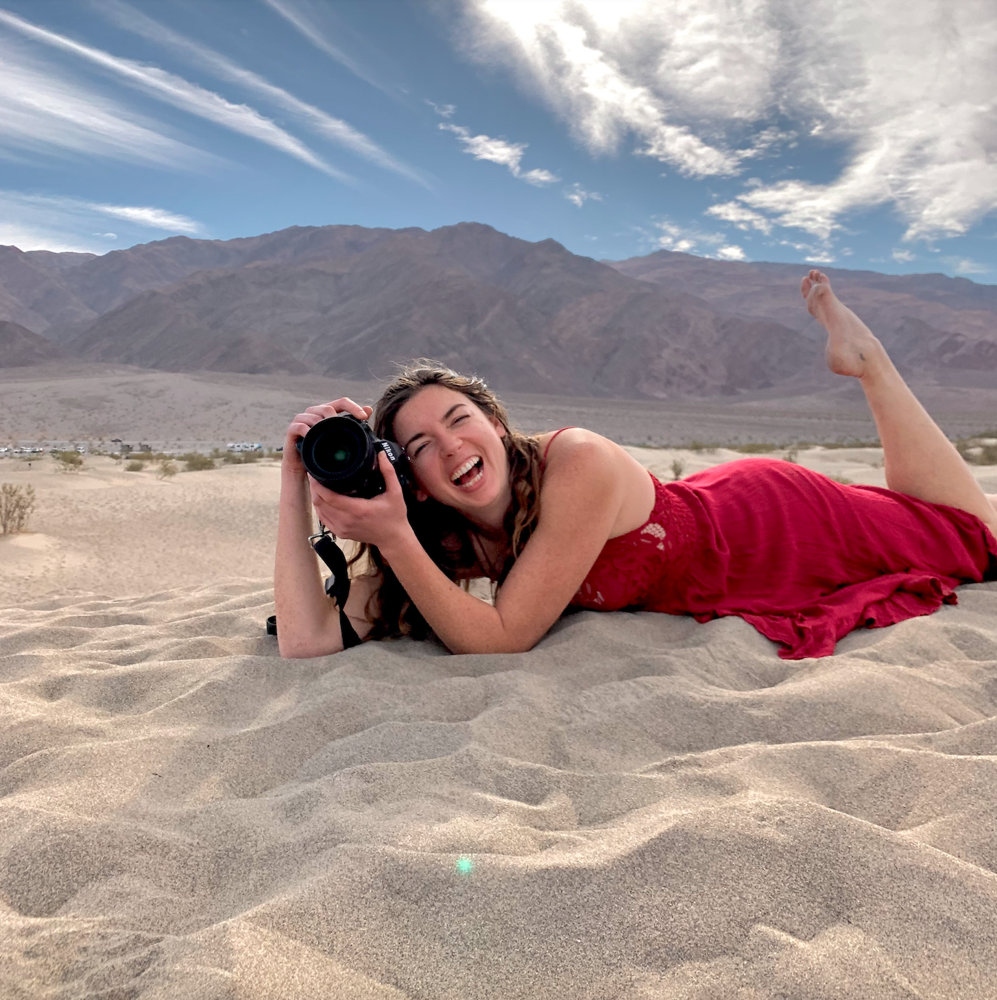 Girl laying in sand with large camera