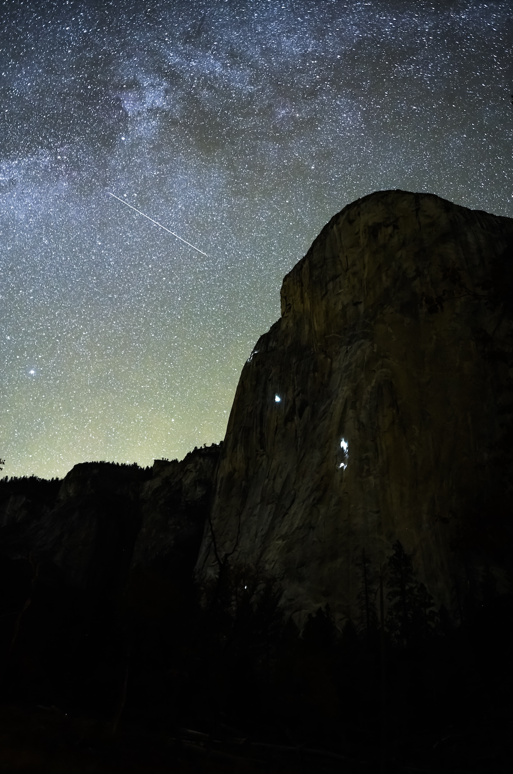 starry night sky and climbers climbing up the side of a mountain