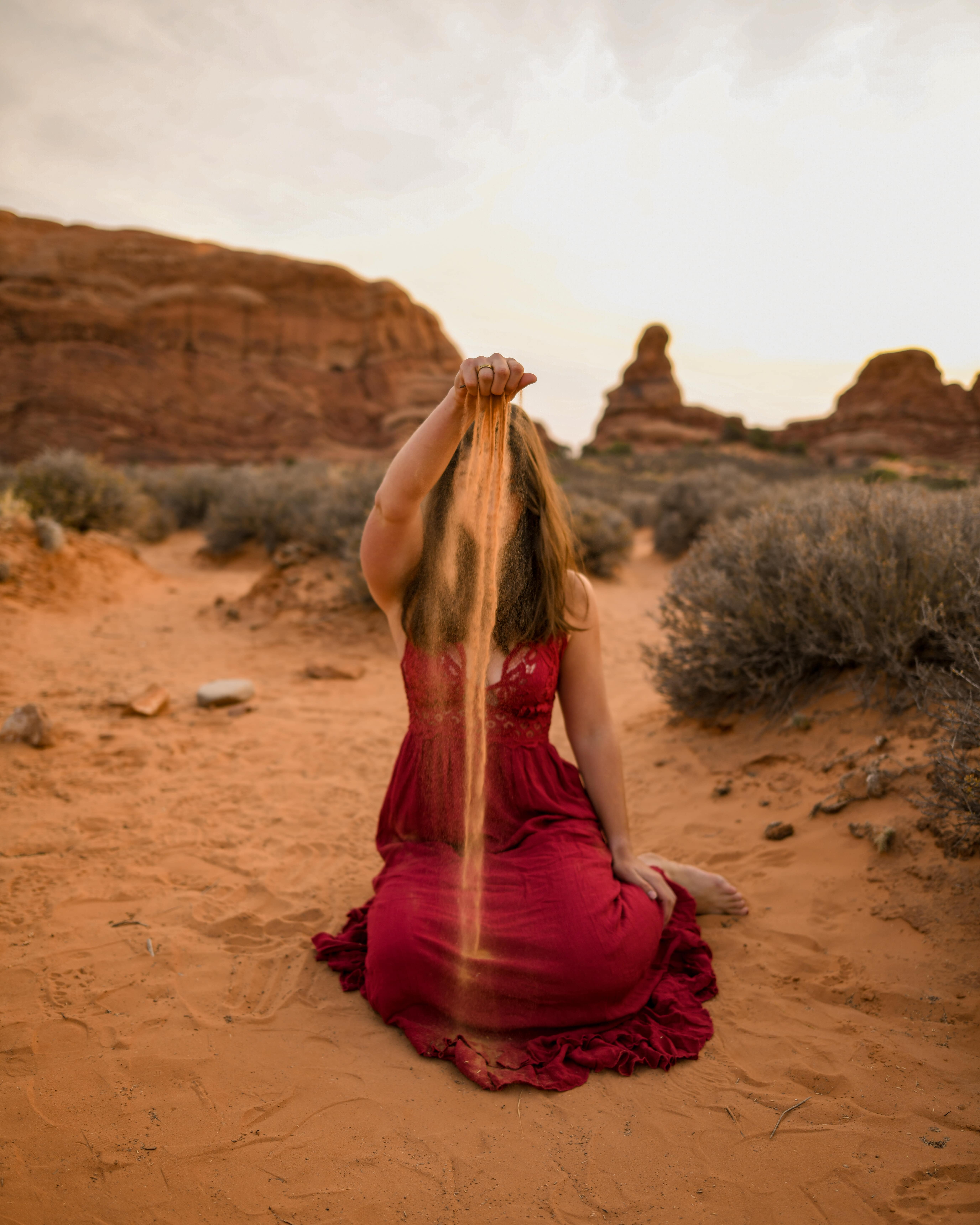 Girl in red dress sitting in sand and sprinkling sand infront of her face