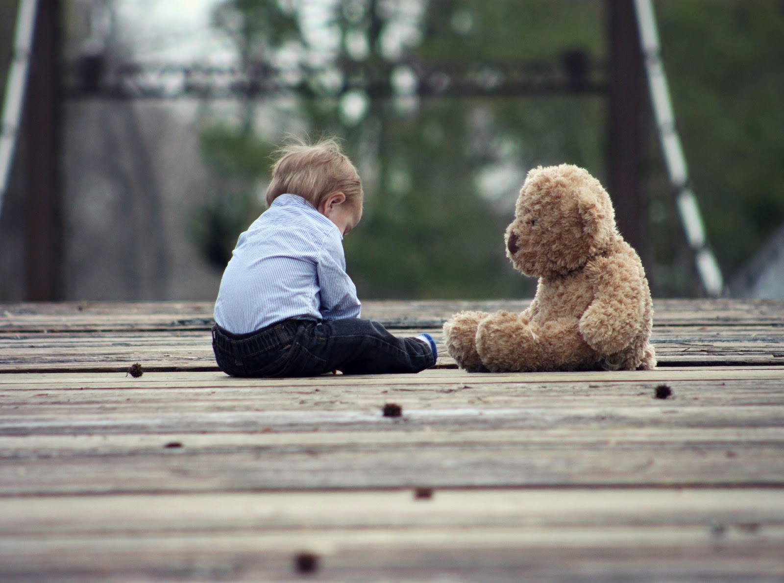 sad child sitting next to teddy bear