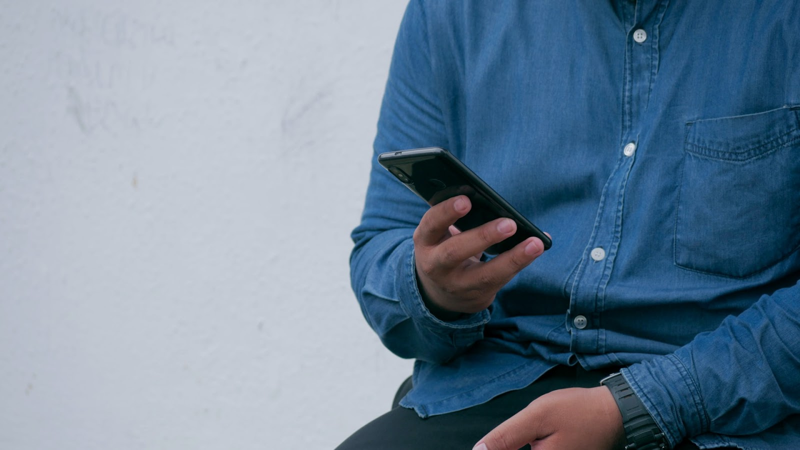 man in blue shirt reading text on cell phone