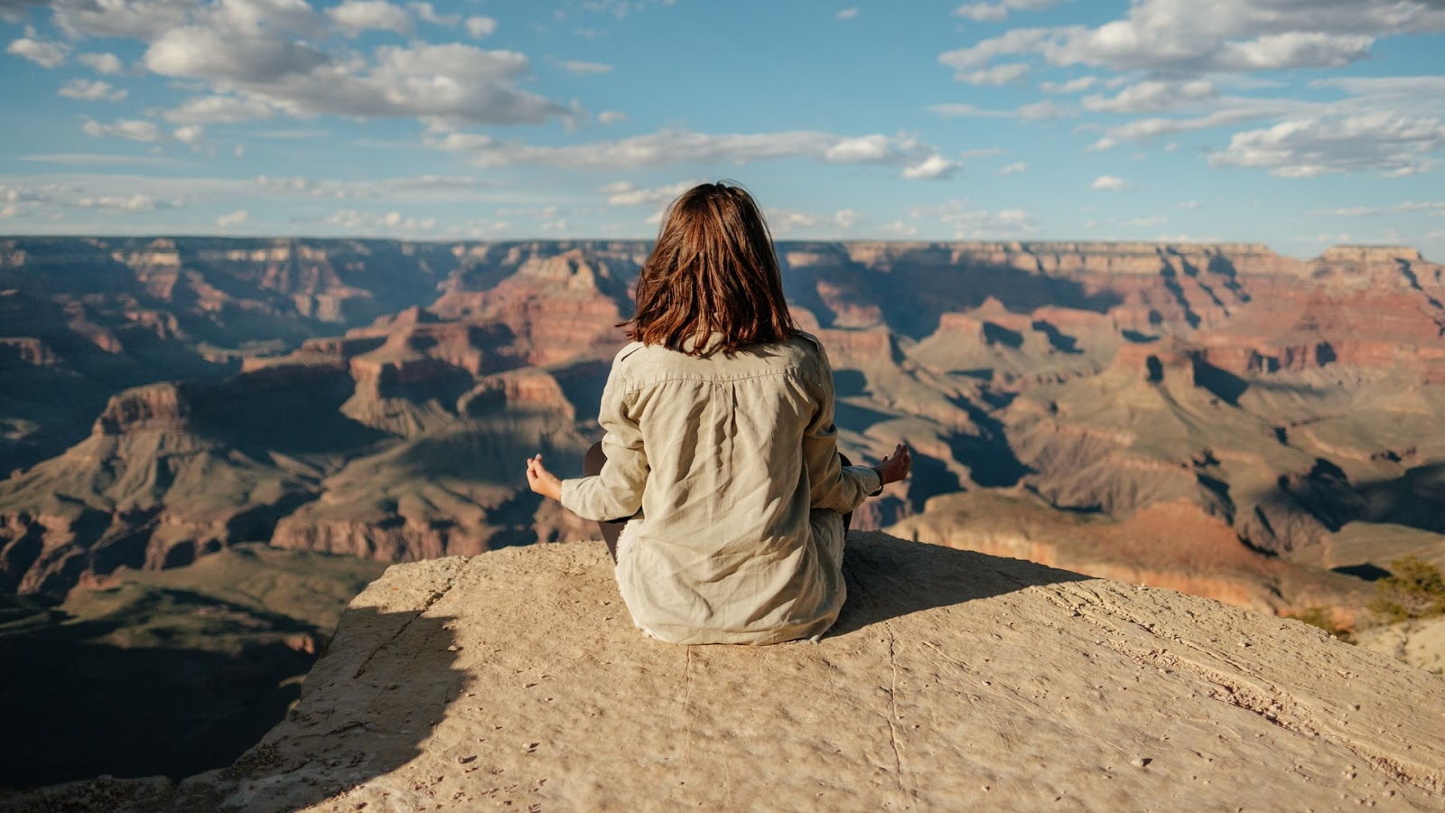 woman meditating on top of a canyon