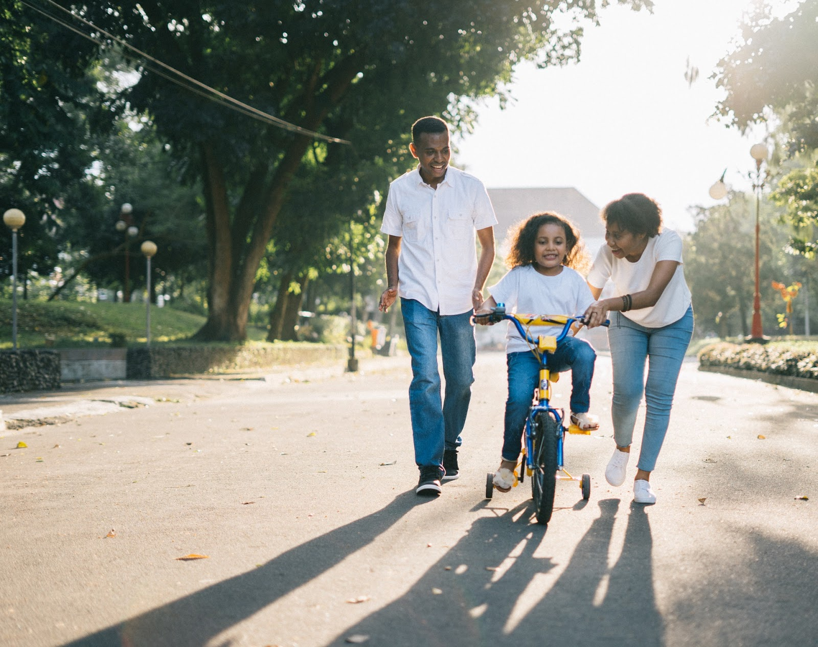 mother and father teaching daughter to ride bike