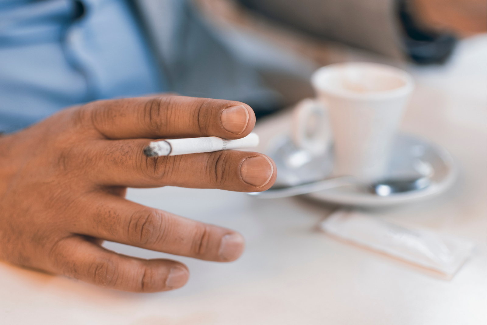 Cigarette in Male Hand With a Cup of Coffee