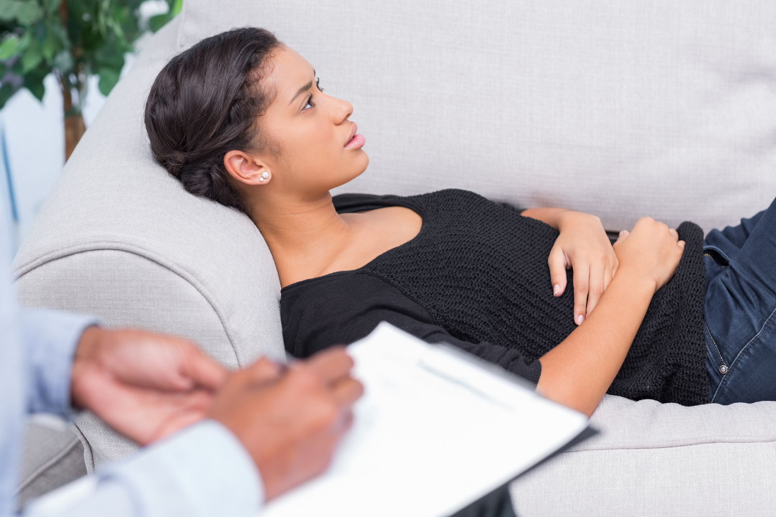 woman lying on sofa talking to therapist