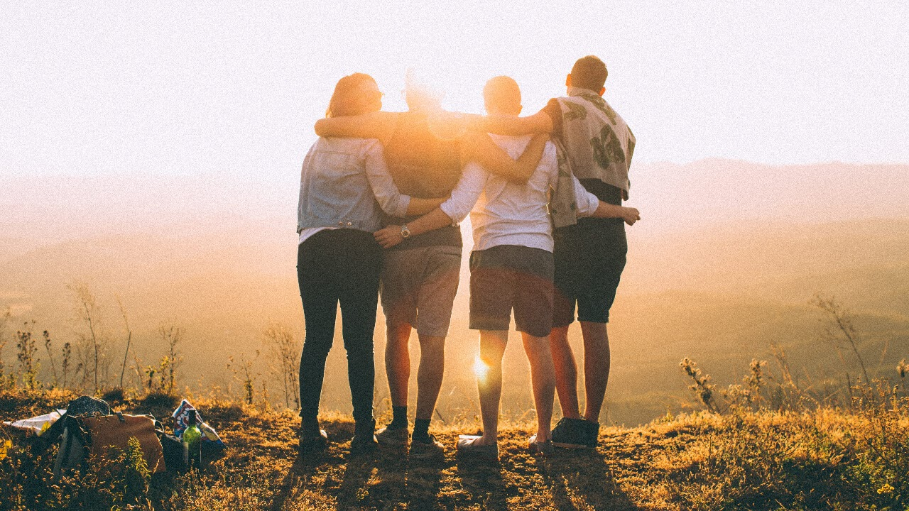 4 friends hugging on a cliff