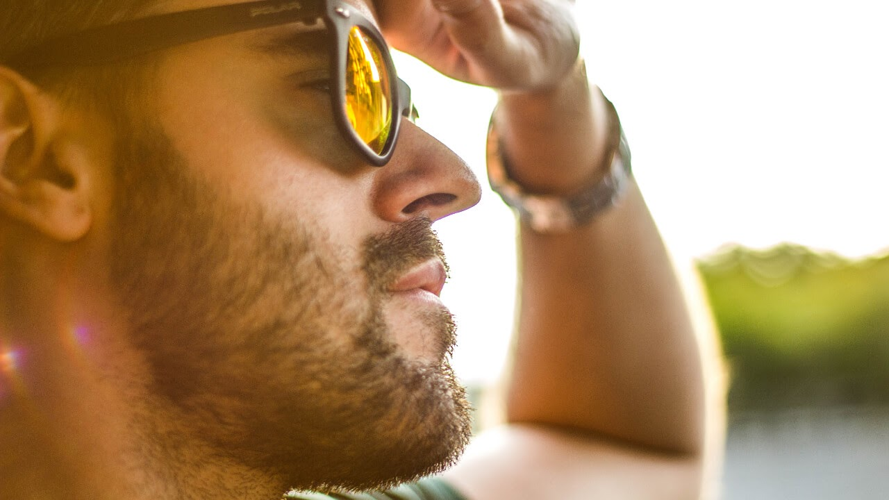 man with facial hair wearing sunglasses in an outdoor setting