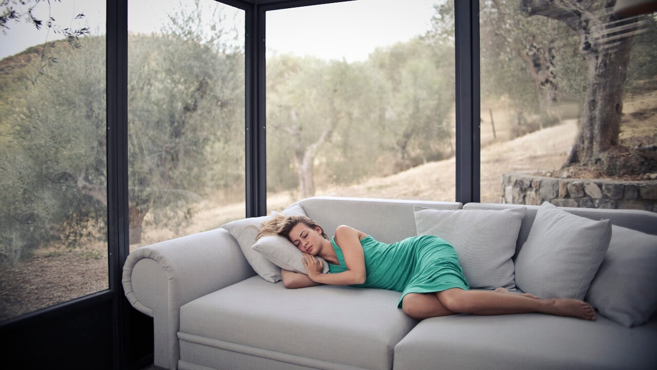 woman in a teal dress sleeping on a white couch