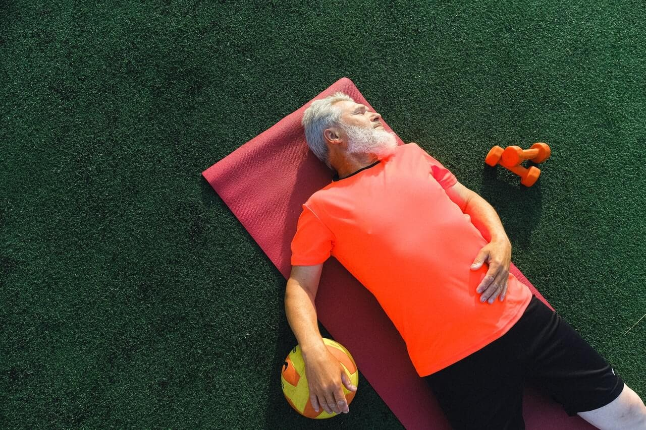 man lying down gray beard orange athletic shirt volleyball green turf weights