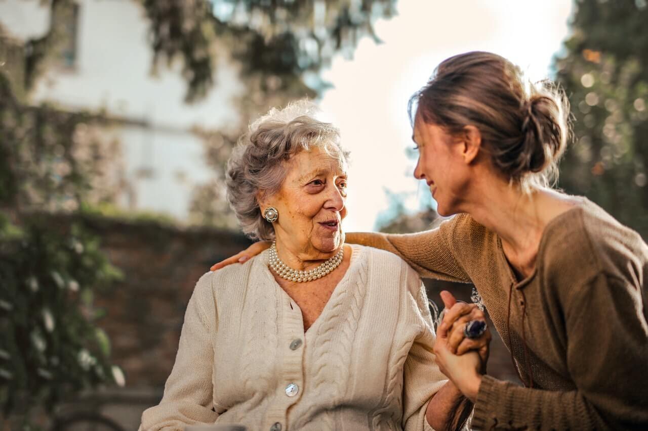 older women speaking conversation friendship sweaters socializing emotional support outside