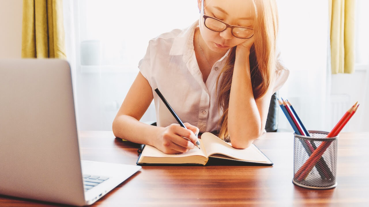 woman studying sunlight desk writing pencils