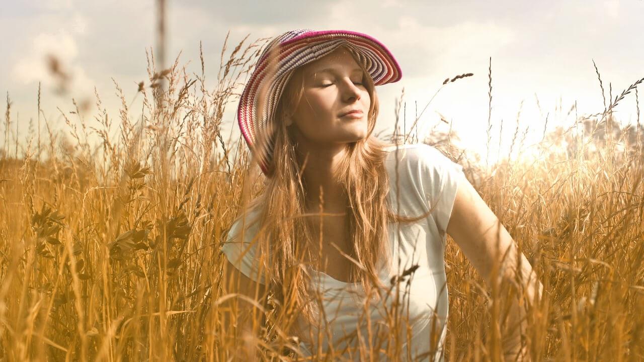 woman breathing striped hat in field wheat sun