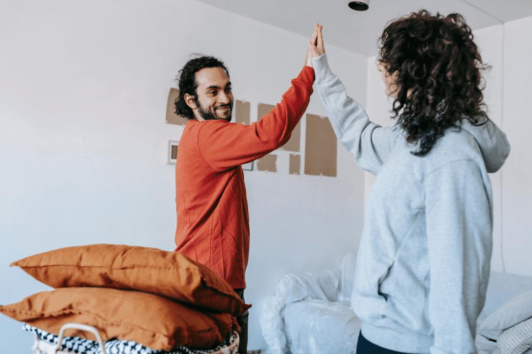 man and woman high fiving orange pillows smiling congratulations accomplishment