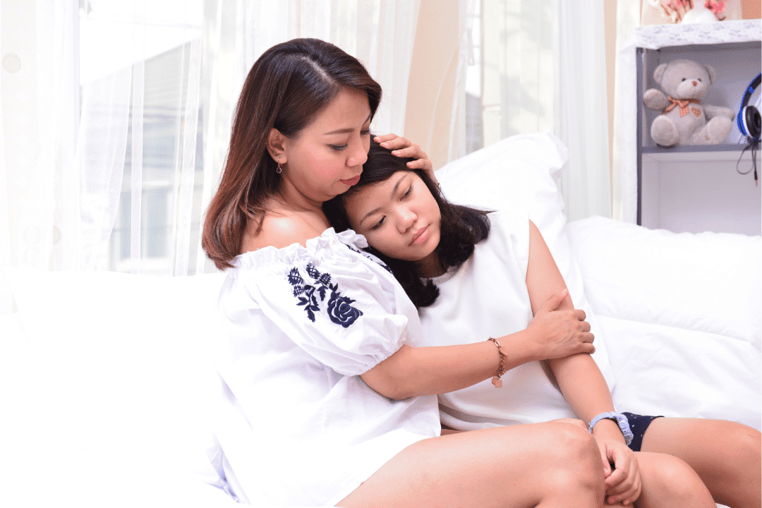 mom and daughter hugging support on bed teen bedroom white sheets open window caring emotional