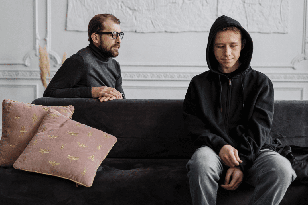 young man in black hoodie with therapist behind couch thick rimmed glasses white walls pillows