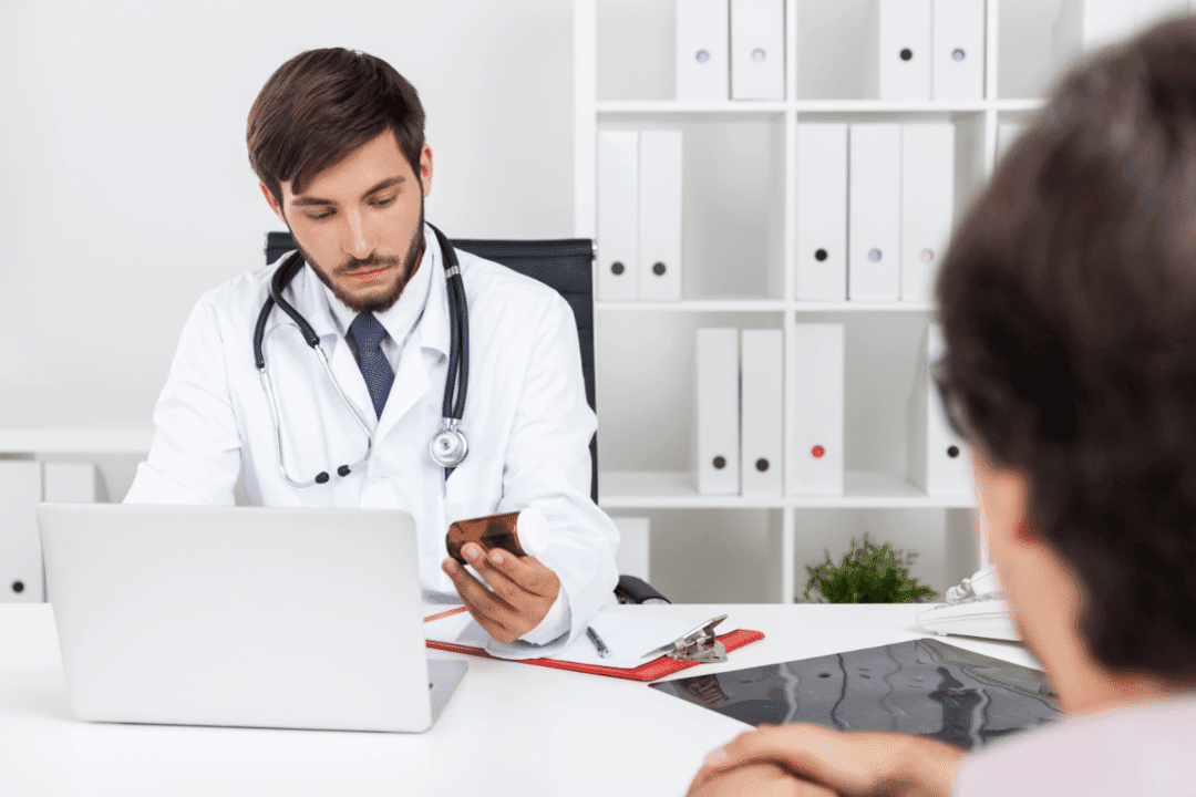 doctor considering side effects on laptop patient consultation binders clipboard stethoscope