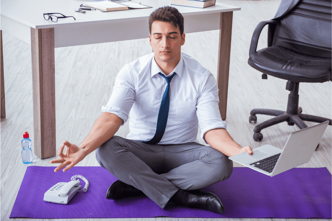 man meditating at office holding laptop purple yoga mat eyes closed sitting on floor telephone shirt and tie