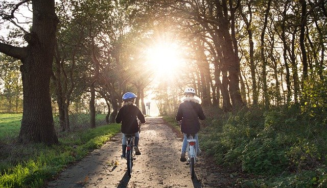 2 girls on bikes riding in the woods