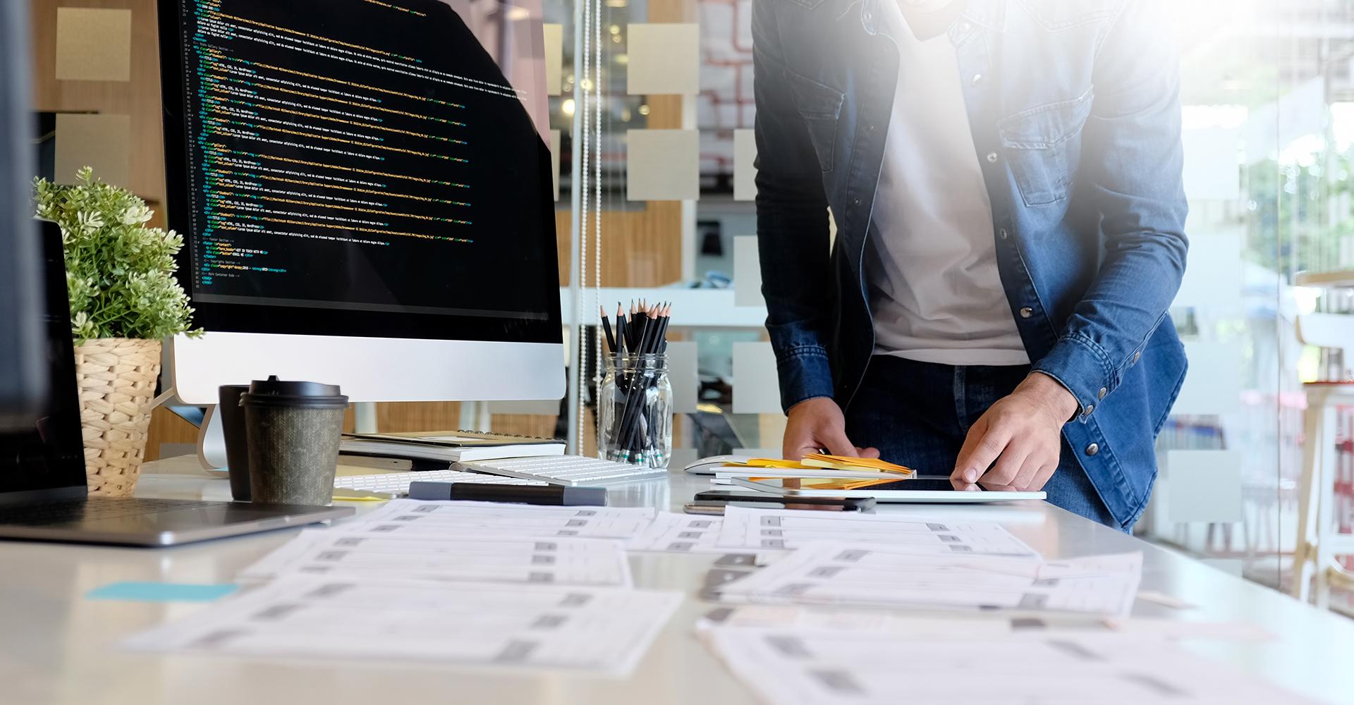 Schreibtisch mit großem PC mit Custom Development, Notizzetteln und Stifte