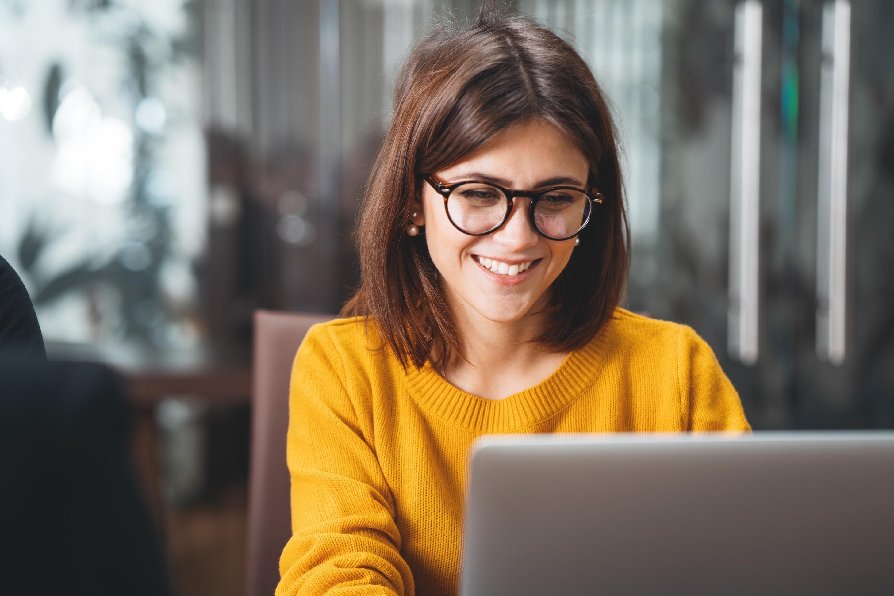 Braunhaarige Person mit gelben Pullover vor Laptop