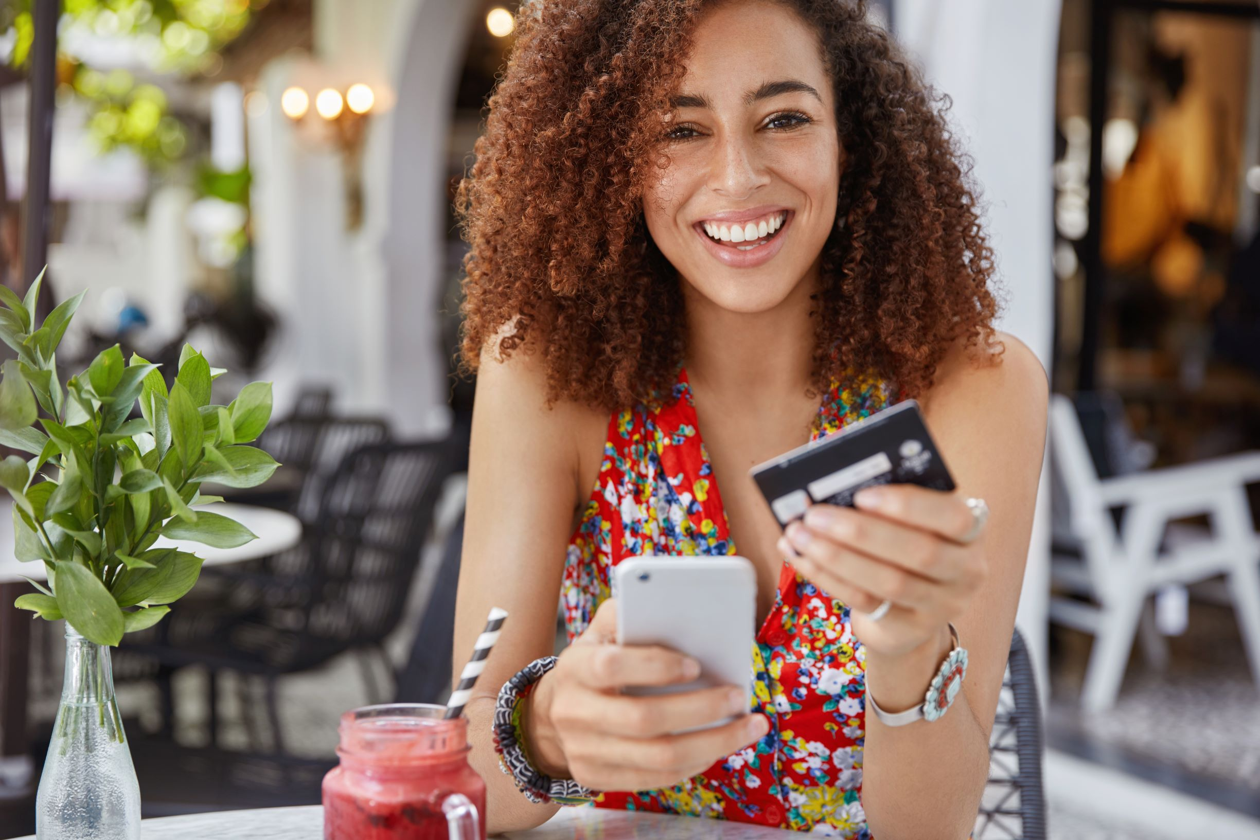 Braunhaarige Frau mit Kreditkarte in der Hand