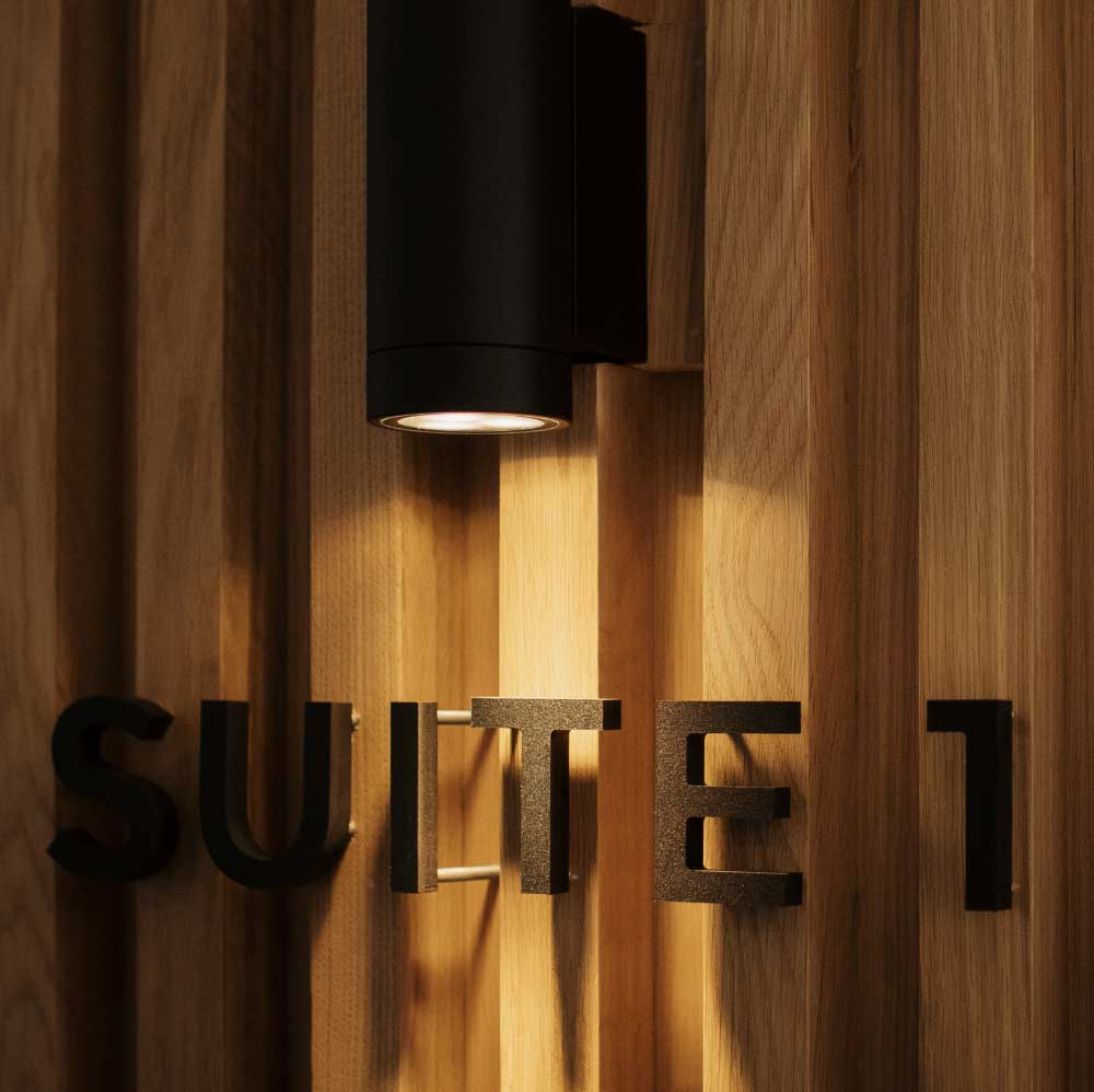 "Photo of a light illuminating a ""suite 1"" sign"