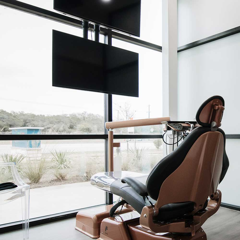 Photo of a dental chair in front of a large window