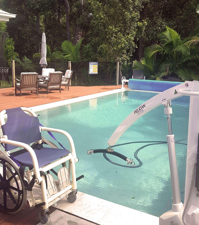 Wheelchair beside pool by pool hoist for wheelchair