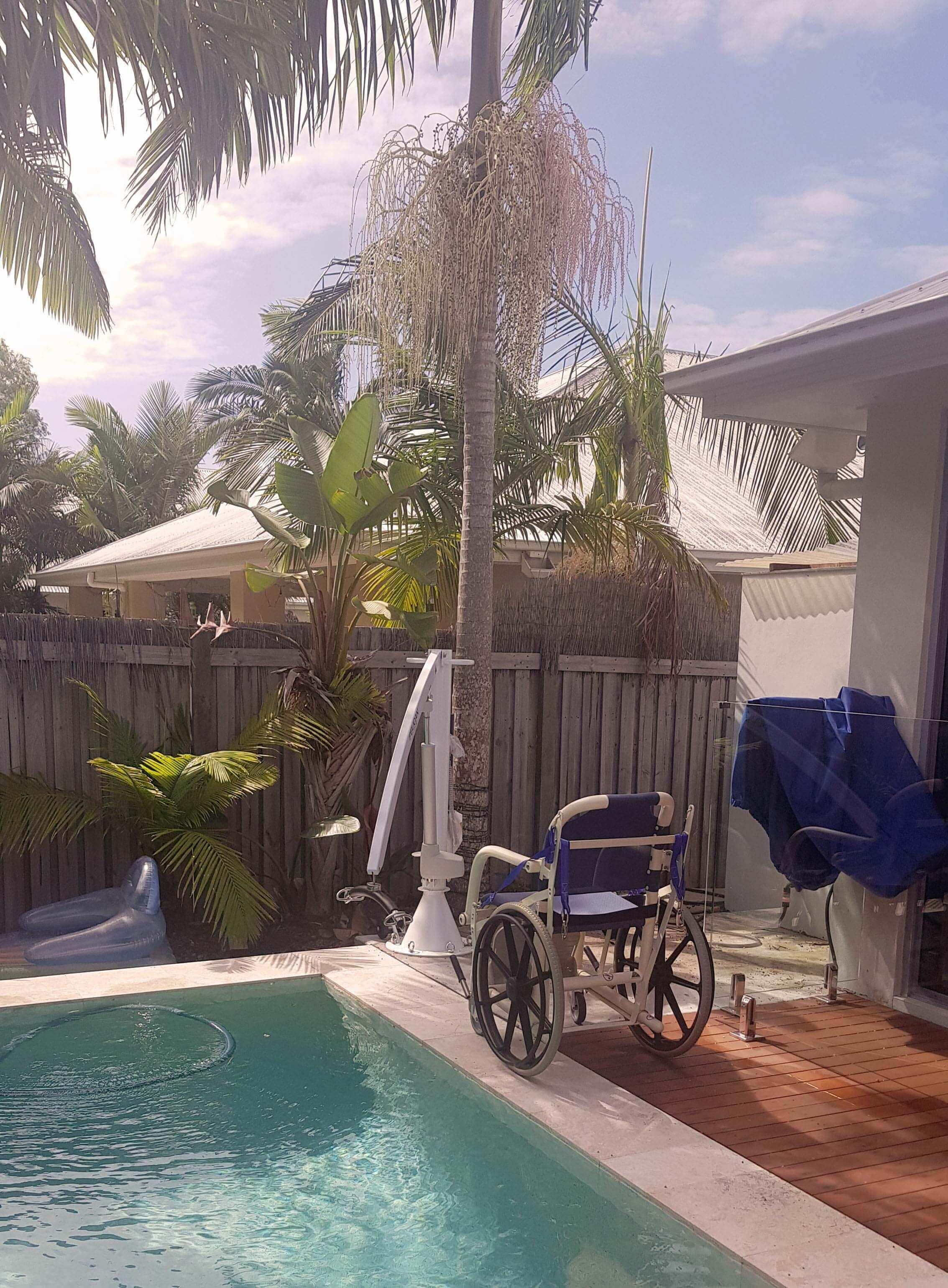 Wheel chair beside wheel chair lift into pool in sunny garden