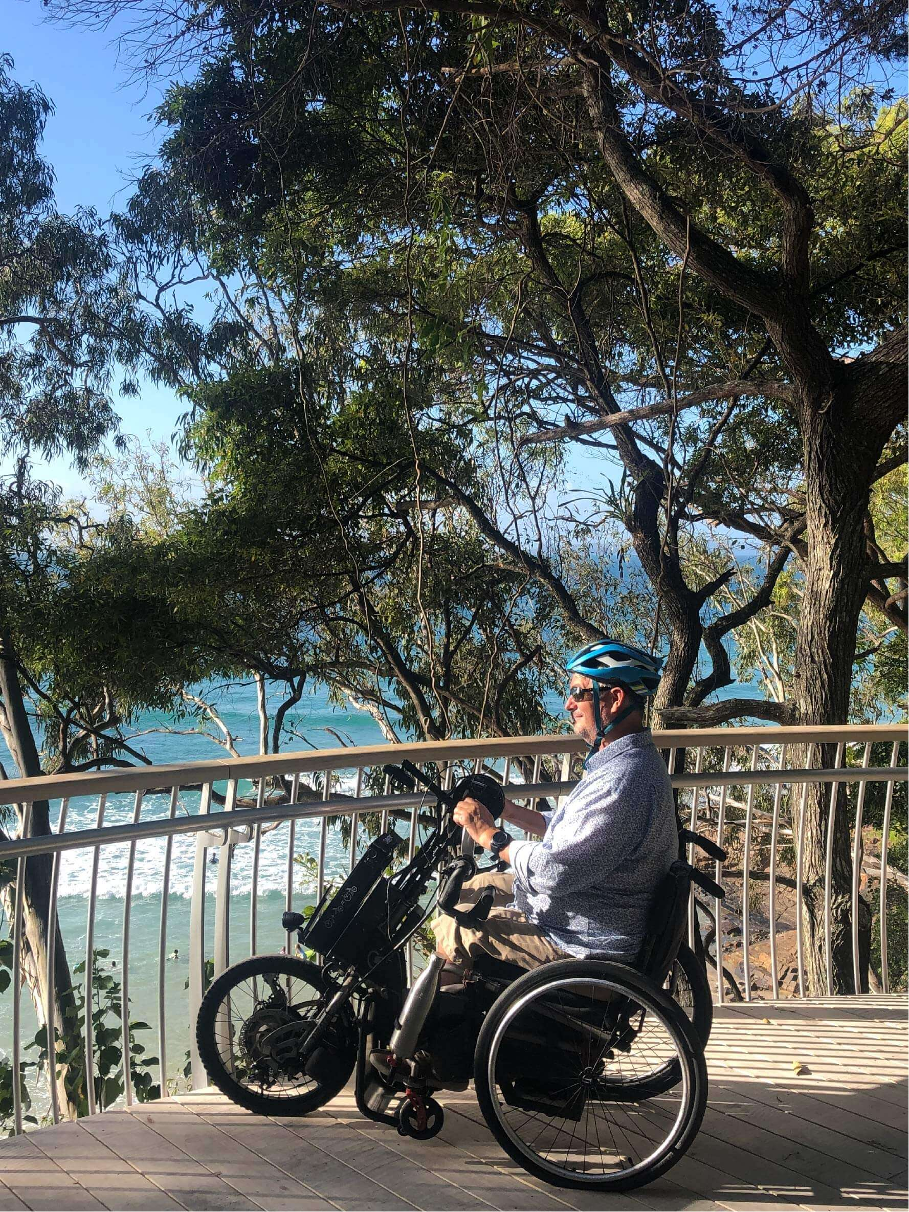 Man smiling in 3 wheeled wheel chair looking over ocean