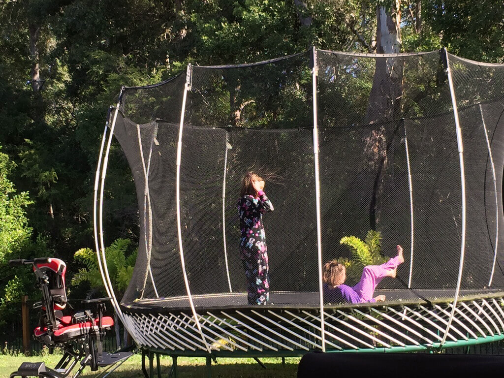 Two children playing on trampoline with wheelchair beside trampoline