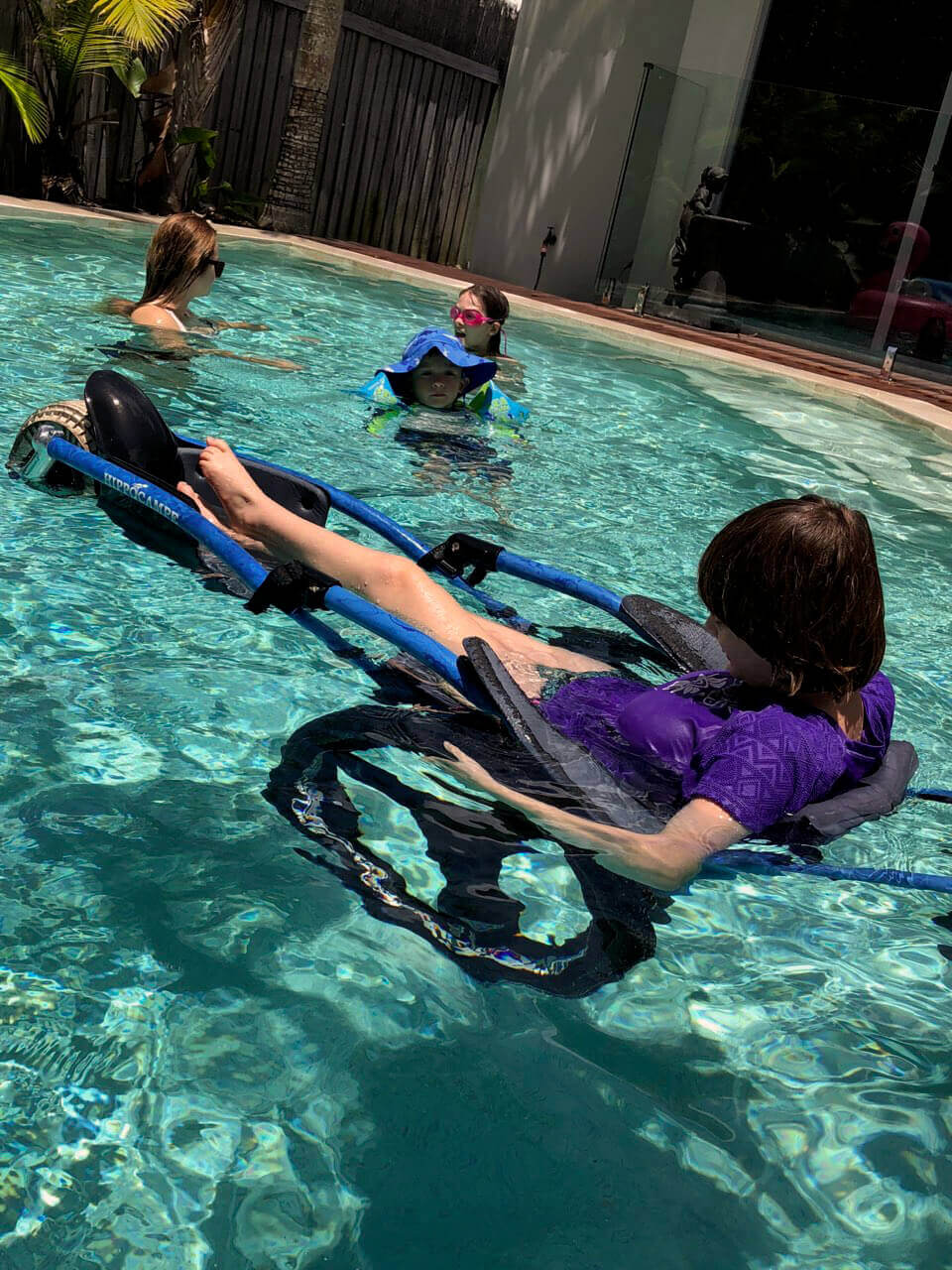 Child in wheelchair designed for swimming pool with 3 other children playing