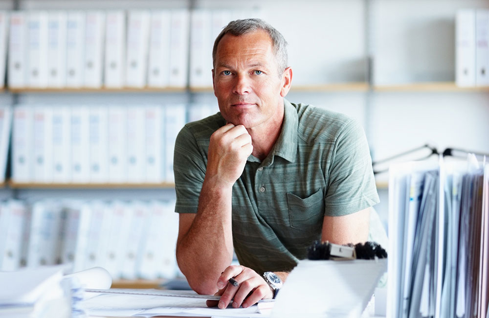 Man surrounded by organized files in binders