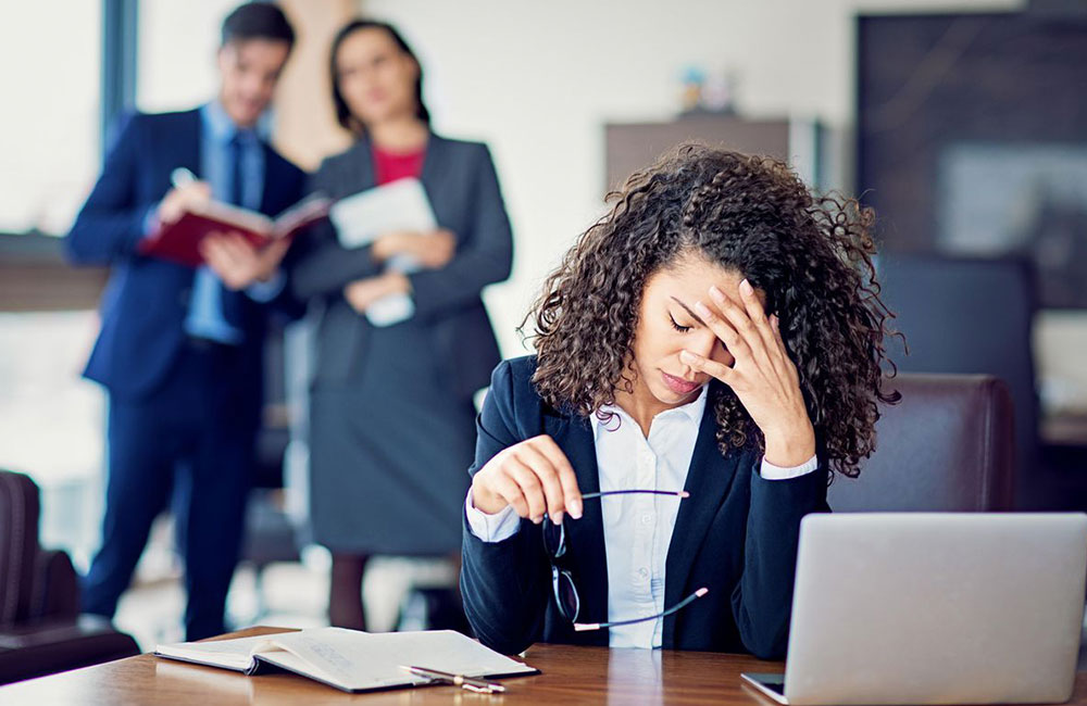 Woman stressed due to office harassment as co-workers talk behind her back