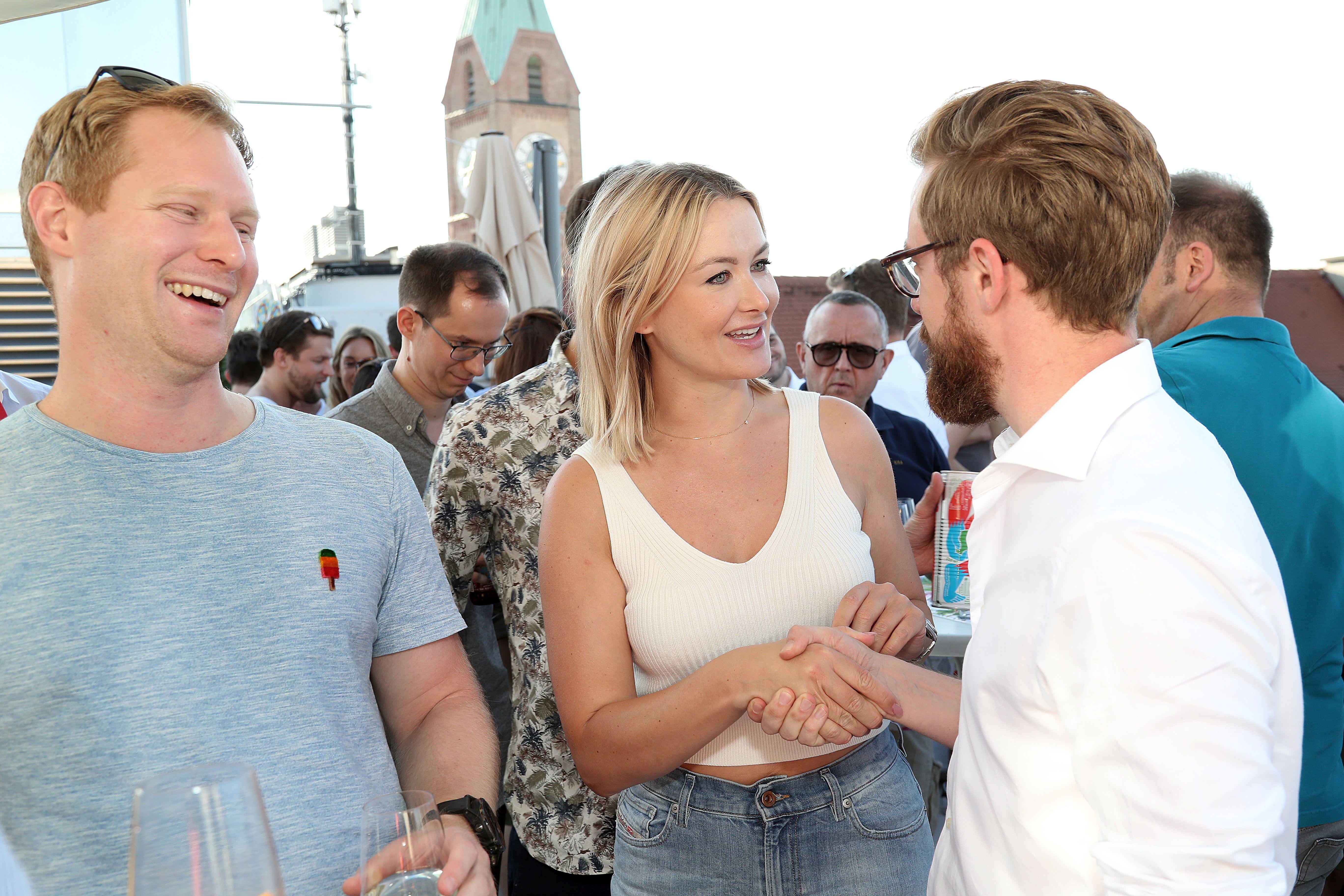 Blonde Frau begrüßt Mann mit Bart und Brille