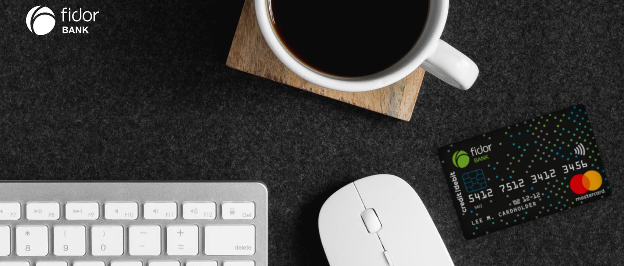 Tastatur, Maus, Tasse und Kreditkarte auf dunklem Hintergrund