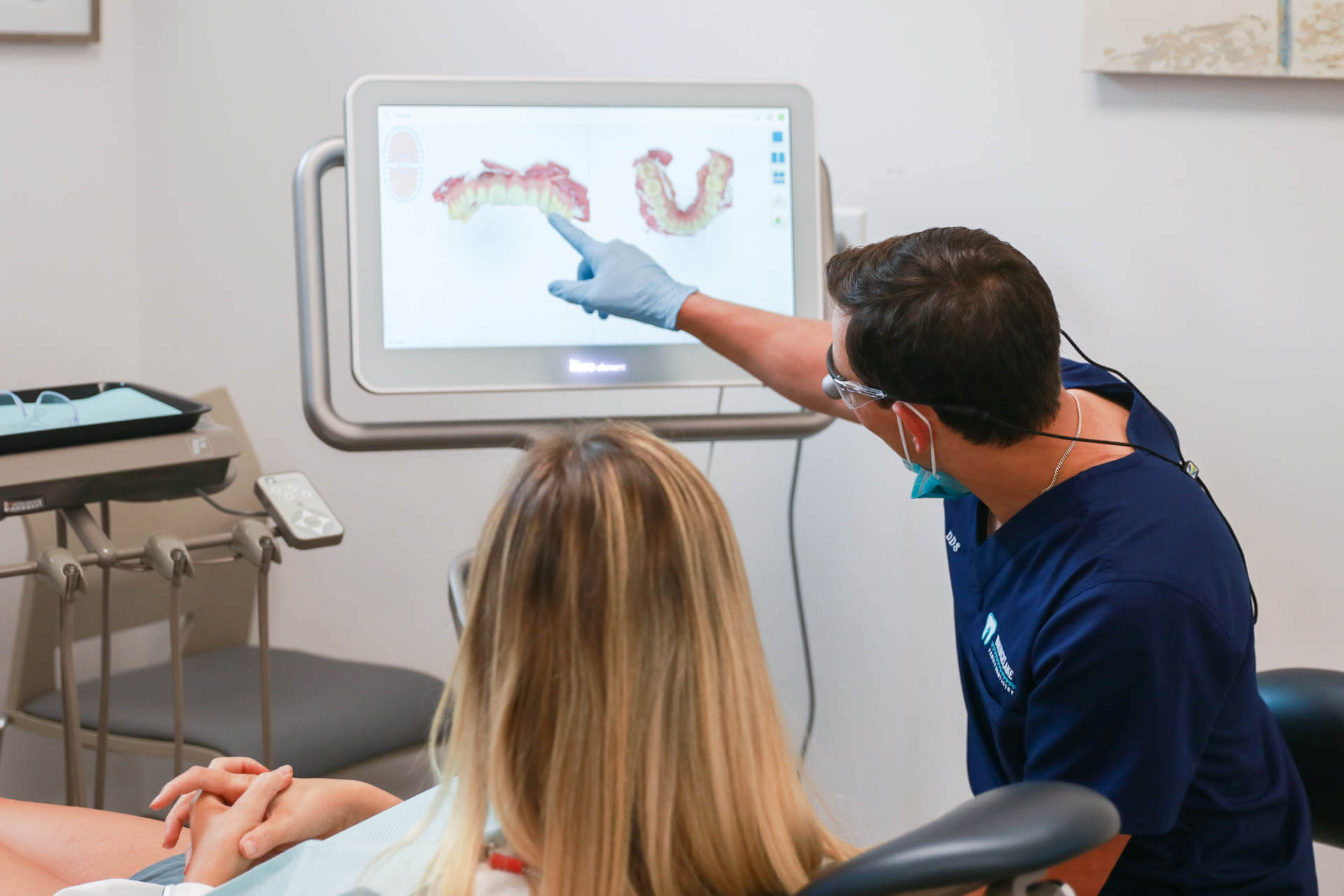 dentist pointing to a 3D scan of teeth