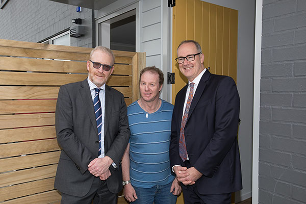 Phil Twyford and Greg Orchard with a tenant outside their home