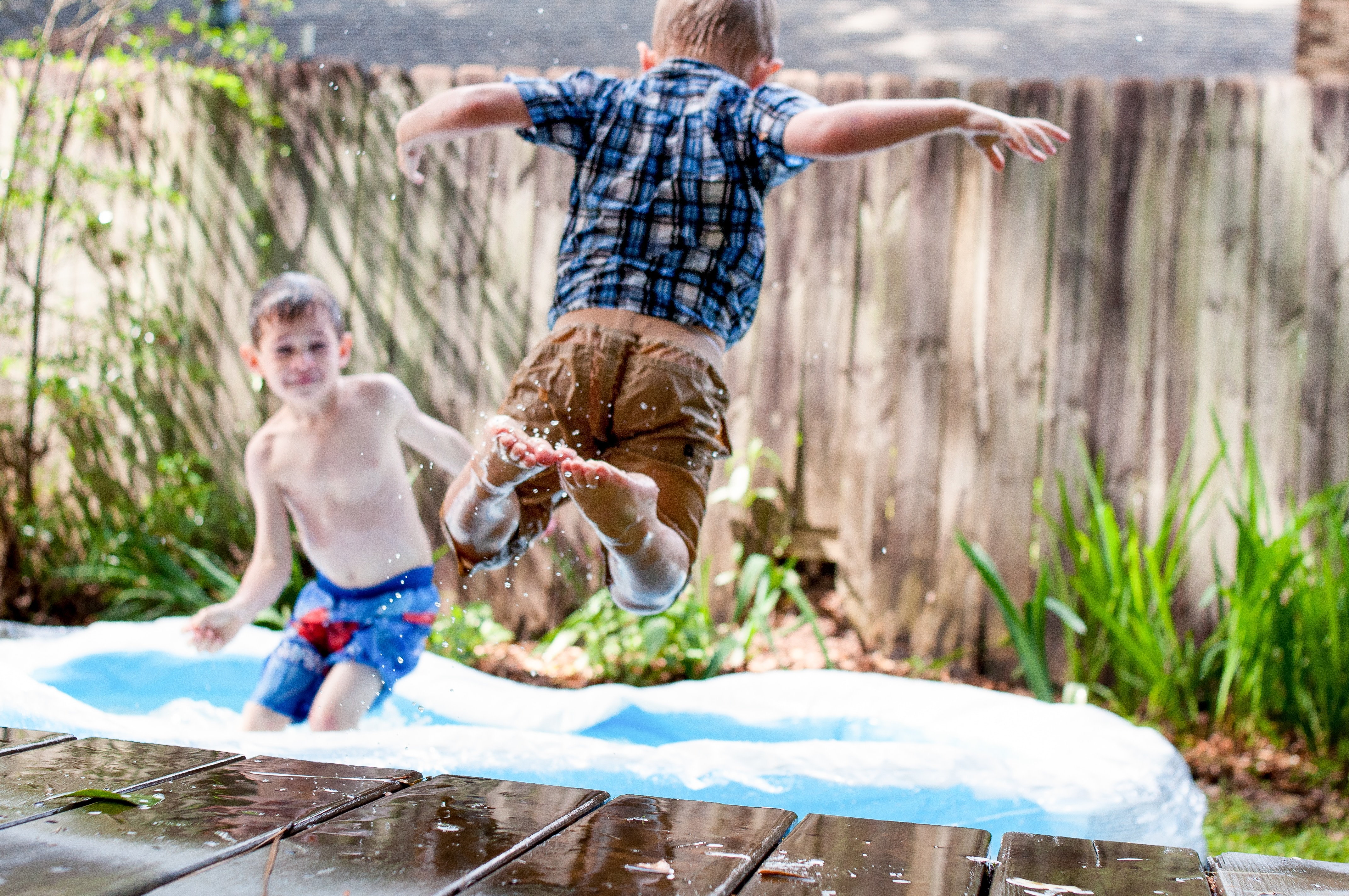 Two kids playing in a paddling pool