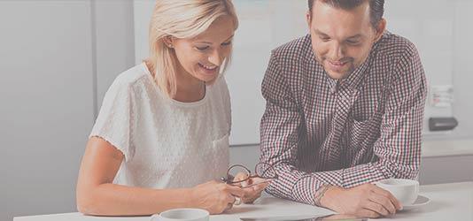Foto Frau und Mann mit Unterlagen und Kaffee