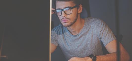 Foto konzentrierter Mann an einem PC nachts