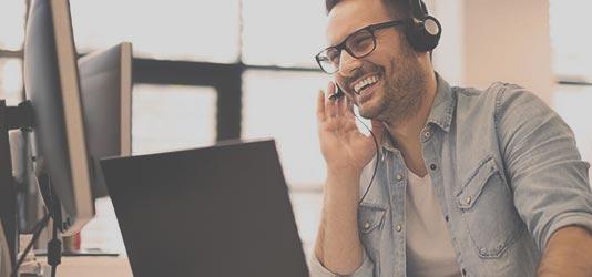 Foto lachender Mann mit Headset am Arbeitsplatz