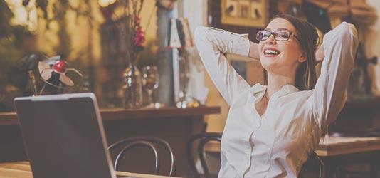 Foto glückliche Frau mit Laptop im Restaurant