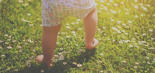 Foto Nahaufnahme Babybeine auf Wiese