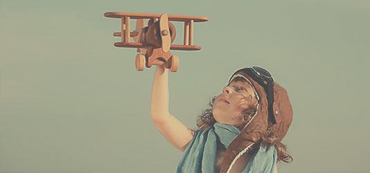 Foto Junge mit Spielzeug Holzflugzeug